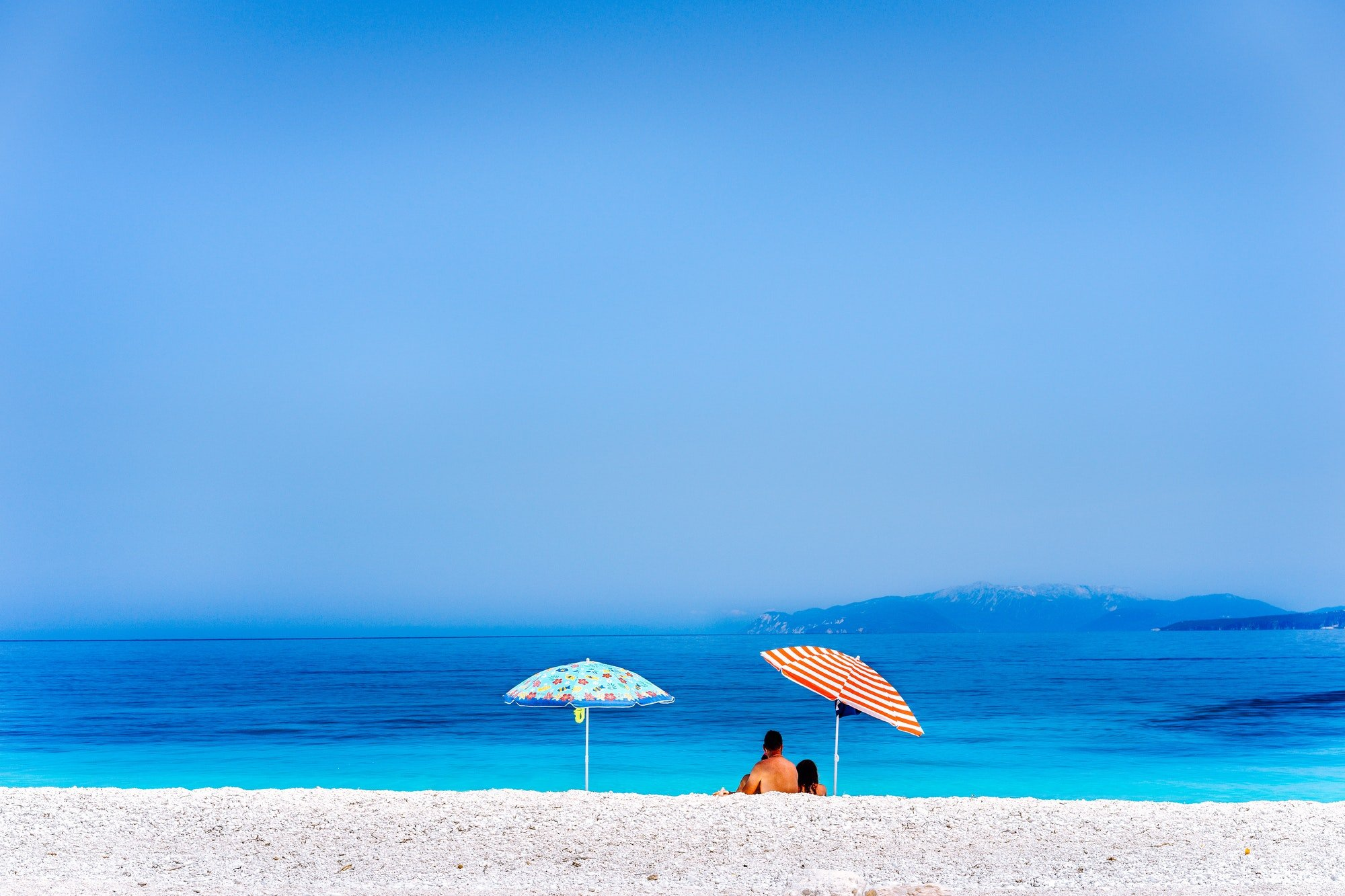 Colorful beach umbrellas crystal clear turquoise sea water paradise hidden beach. Summer concept